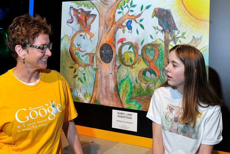 "Eighth-grader Isabel Robertson chats Wednesday with her art teacher, Marguerite Lawler-Rohner, in front of a blow-up of her winning drawing in a Google ""doodling"" contest. Isabel will represent Maine at the New York City finals in two weeks, going as a guest of Google."