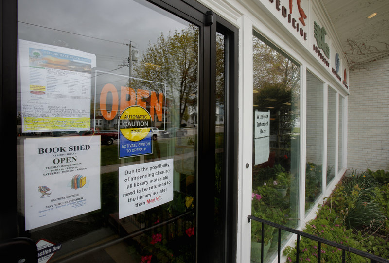 A sign on the door of the Libby Memorial Library in Old Orchard Beach, pictured Wednesday, asks patrons to be prepared to bring back all library material by May 9 because of the possibility of the library closing.