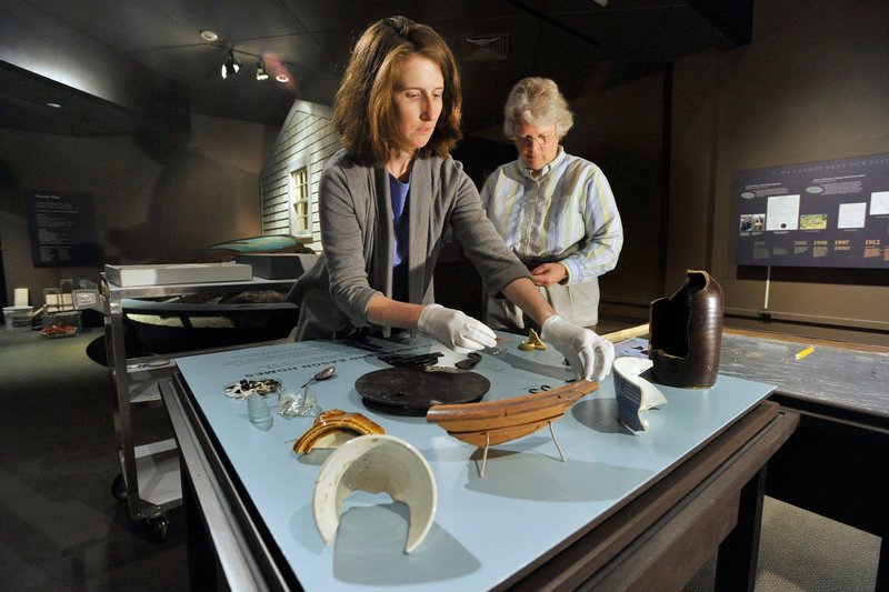 "Kate McBrien and Linda Carrell arrange artifacts from Malaga Island for the exhibit ""Malaga Island, Fragmented Lives"" at the Maine State Museum in Augusta."