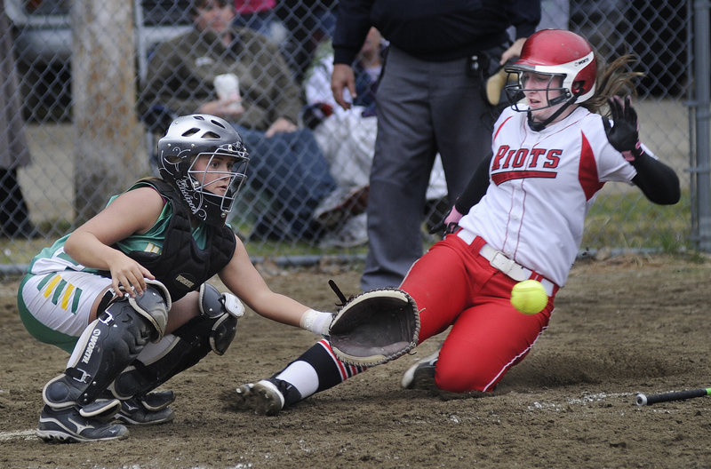 Sam DiBiase of South Portland slides safely into home as Massabesic catcher Amber Libby waits for the throw during South Portland's 17-0 softball victory Wednesday.