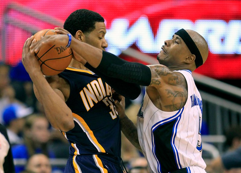 Quentin Richardson of Orlando, right, tries to get the ball away from Indiana's Danny Granger in Wednesday night's playoff game at Orlando, Fla. The Pacers won, 97-74.