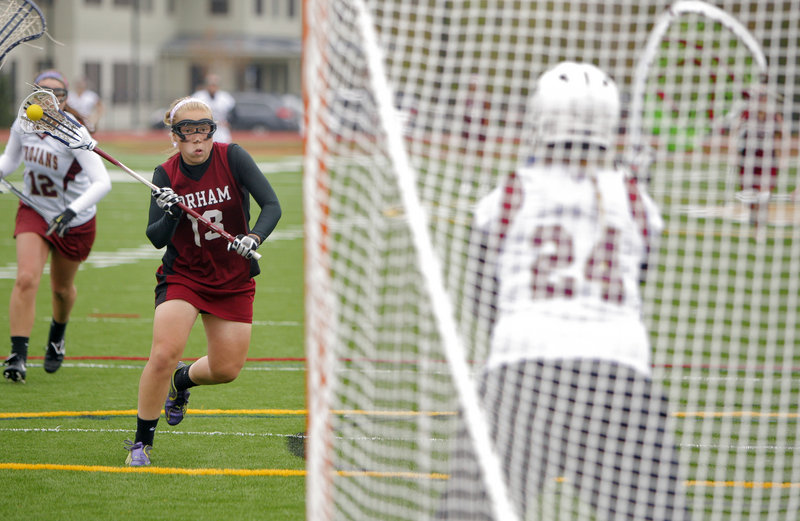 Meghan Cushing of Gorham advances against Thornton Academy goalie Alexandria McCarthy to score the goal that made it 9-9. Gorham went on to an 11-10 victory in a schoolgirl lacrosse game Thursday.