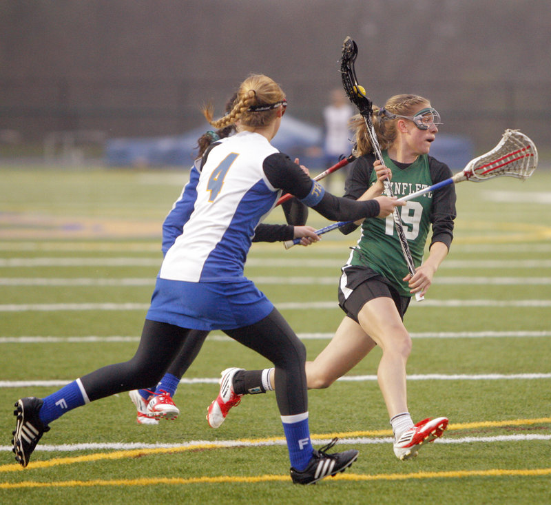 Martha Veroneau of Waynflete carries the ball toward the goal while being chased by two Falmouth players, including Ashleigh Burton, front. Veroneau finished with four goals and two assists, helping the Flyers to a 13-10 victory.
