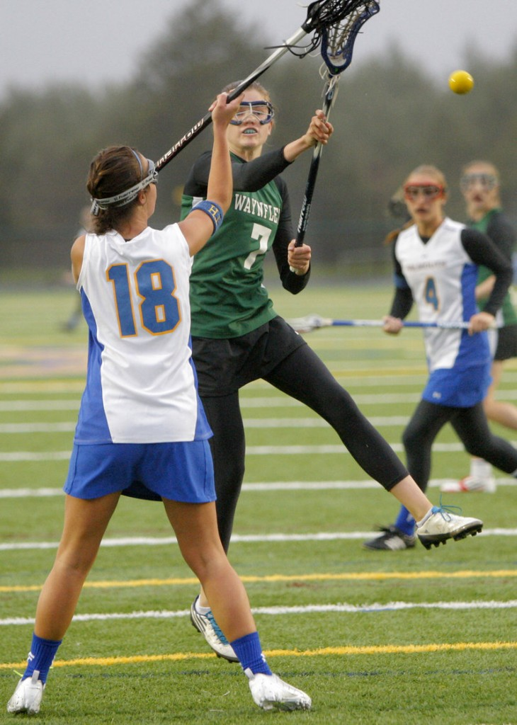 Walker Foehl of Waynflete fires a shot for one of her four goals Friday against Falmouth despite the defense of Vanessa Audet. Waynflete improved to 6-0 and handed Falmouth its first loss, 13-10.