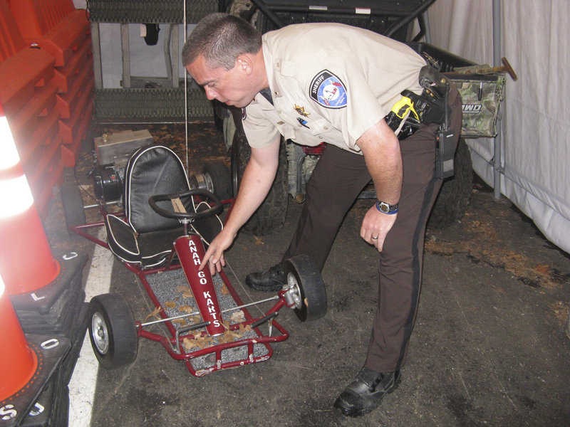 Lincoln County Sheriff's Office Lt. Rand Maker points to frame damage on the go-cart driven by Marvin Tarbox, who was killed last year when the vehicle was in an accident while he was performing a stunt in the Damariscotta Pumpkinfest Parade.