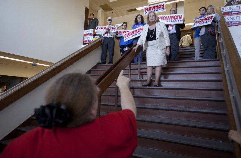 U.S. Senate candidate Debra Plowman takes a question while giving a speech from a stairway. Other Senate candidates whose speech time was eliminated did something similar.