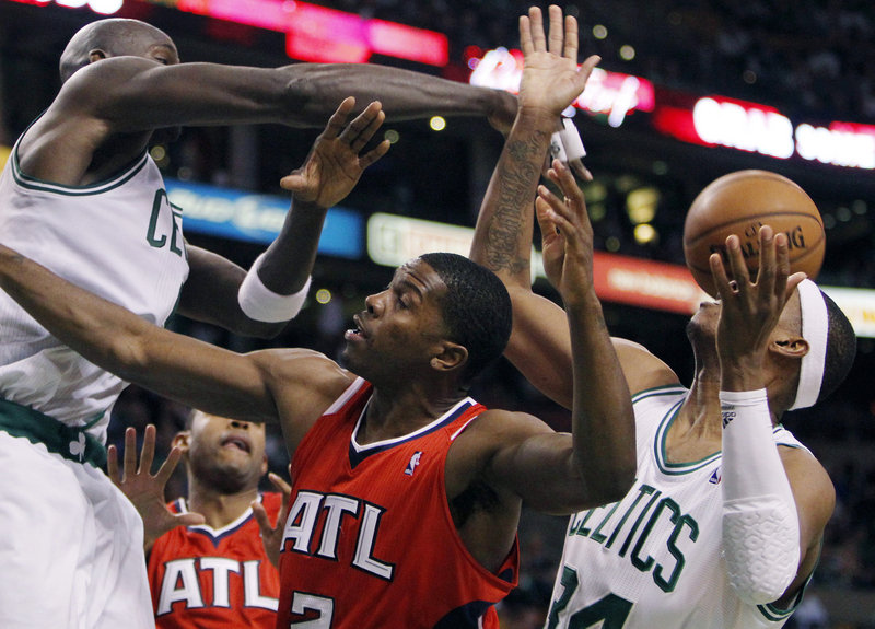 Atlanta's Joe Johnson, center, loses control of the ball between Boston's Kevin Garnett and Paul Pierce during Game 4 of their Eastern Conference first-round series Sunday night. The Celtics led by as many as 37 points on the way to a 101-79 win.