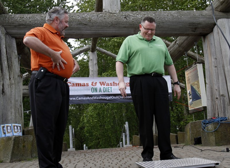 "Washougal, Wash., Mayor Sean Guard, left, coaxes Camas Mayor Scott Higgins to step on the scales during a weigh-in this month. The mayors of the two neighboring towns are in a ""Biggest Loser""-style contest to see which of the two communities can lose the most weight."