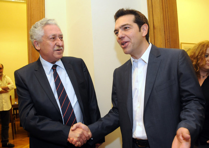 The Greek leader of Coalition of the Radical Left party, Alexis Tsipras, right, and leader of the Democratic Left party, Fotis Kouvelis, greet each other before their meeting at the Greek Parliament in Athens on Tuesday. Greece's commitment to austerity is no longer valid because voters have rejected those deals, Tsipras declared Tuesday as he tried to form a new coalition government.