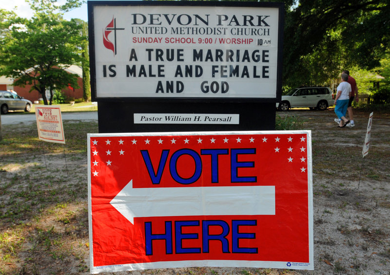 The messages on signs were all about religion and politics Tuesday in front of the Devon Park United Methodist Church election site in Wilmington, N.C., as voters went to the polls.