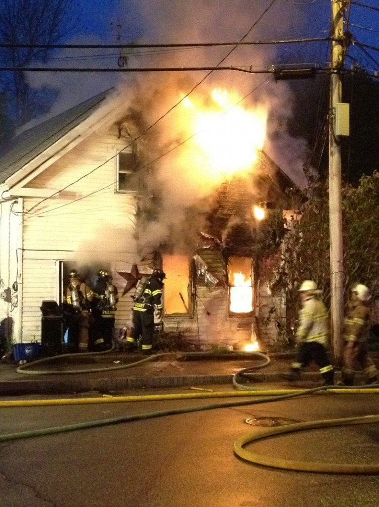 Fire engulfs a home at 55 Common St. in downtown Saco on Wednesday night. No one was injured in the blaze.