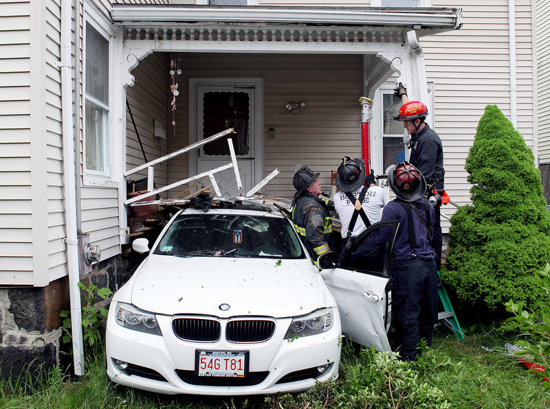Boston firefighters work to support the porch of a home after an 8-year-old boy backed his mother's BMW out of their driveway across the street and crashed it Wednesday. No one was hurt.