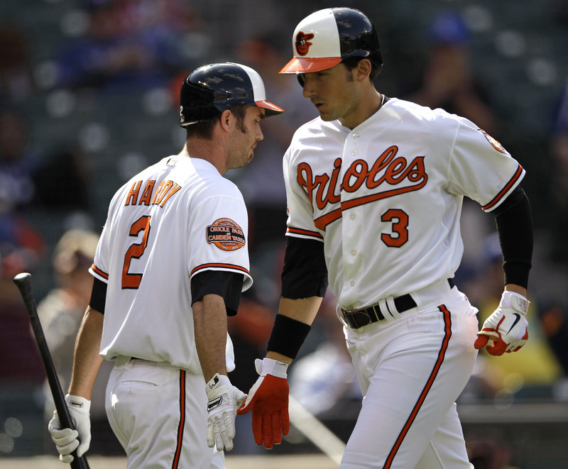 Ryan Flaherty, right, of the Orioles is congratulated J.J. Hardy after hitting a solo homer in the first inning of the opener of their doubleheader against the Rangers on Thursday. Flaherty, a former Deering High standout, went a combined 2 for 5 in the games.