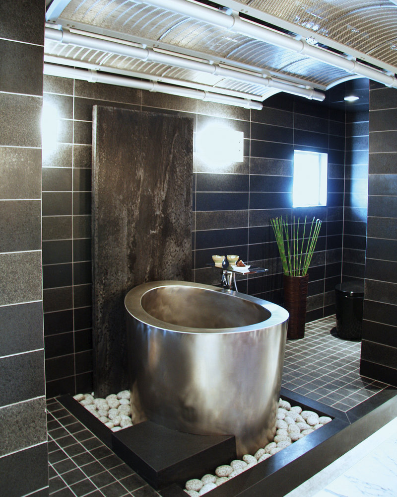 A stainless steel elliptical soaking tub from Diamond Spas is situated among white river rocks in a sleek, Asian-inspired tiled bath.