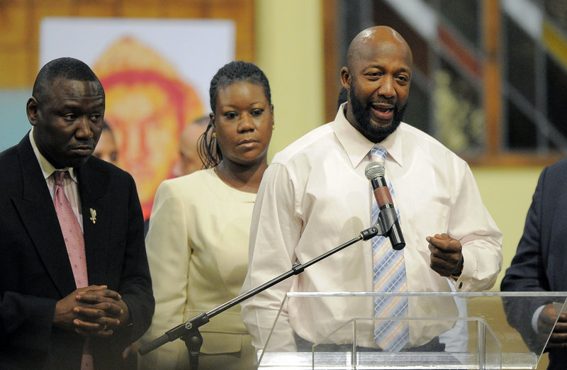 Tracy Martin, right, speaks as Sybrina Fulton, center, and attorney Benjamin Crump look on during a rally on behalf of the family of shooting victim Trayvon Martin in April.