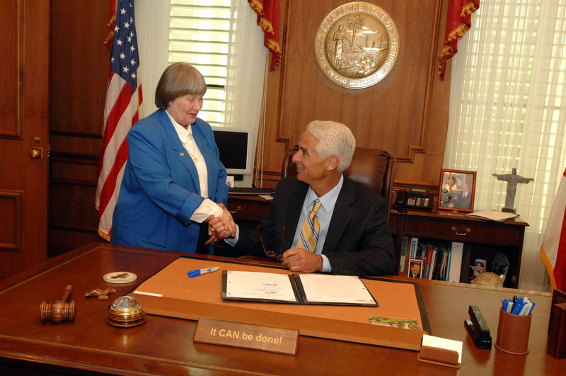 NRA lobbyist Marion Hammer shakes hands in 2008 with Florida Republican Gov. Charlie Crist after passage of a law that lets workers store firearms in their cars while at work.