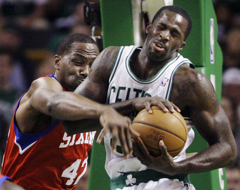 Brandon Bass of the Boston Celtics controls a first-quarter rebound Saturday night as Elton Brand of the Philadelphia 76ers reaches.