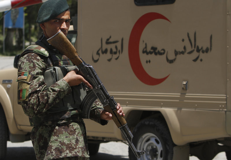 An Afghan soldier patrols the gate of a Kabul military hospital Sunday after a former high-ranking Taliban official who was working to end the war in Afghanistan was assassinated in one of the capital's most secure areas.