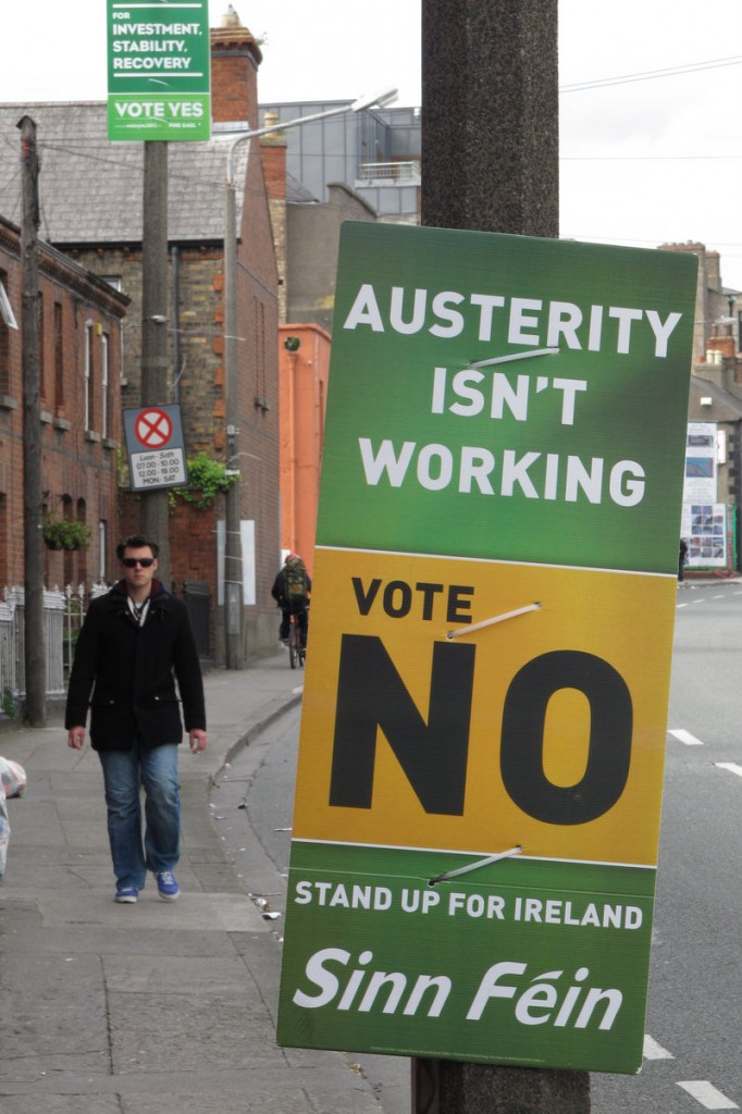 A man walking down a street in Dublin on Sunday passes rival referendum posters advising