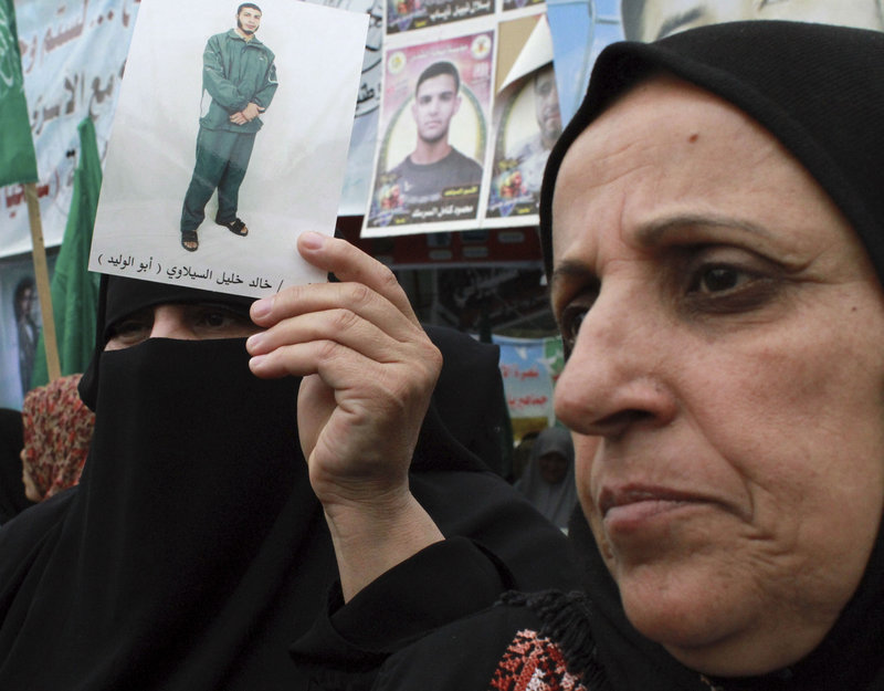 Palestinian women, one holding a photograph of a prisoner, participate in a solidarity protest with Palestinian prisoners jailed by Israel, in Gaza City on Monday.