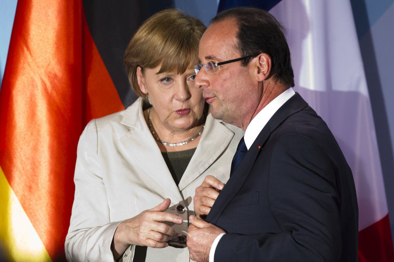 German Chancellor Angela Merkel talks to French President Francois Hollande after a news conference Tuesday in Berlin. They met for the first time since Hollande took office.