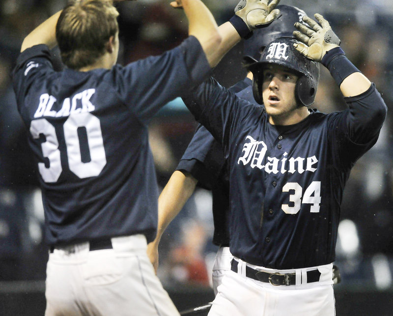 Tyler Patzalek of the University of Maine, right, is greeted by teammate Troy Black after scoring during a four-run seventh inning in a 9-4 victory over Boston College.