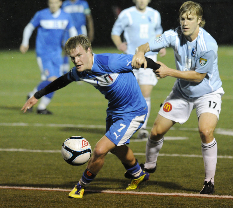 Nathaniel Simons of the Brooklyn Italians, left, is held back by Sean Hoek of the Portland Phoenix during their U.S. Open Cup game Tuesday night at Deering High. Brooklyn won, 3-2.