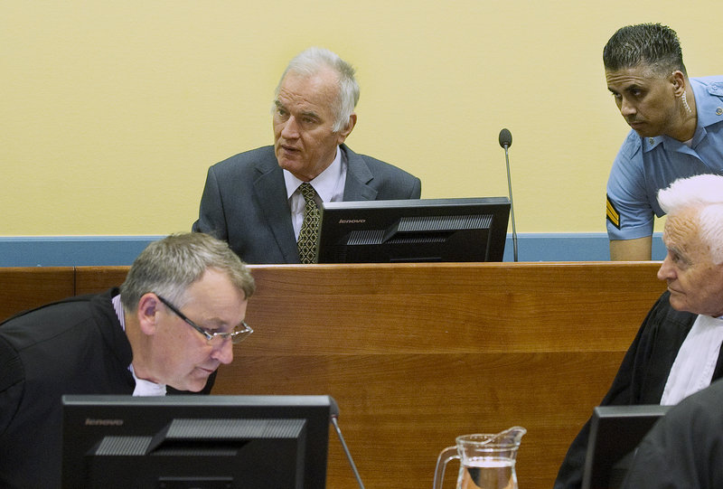 Former Bosnian Serb military commander Gen. Ratko Mladic, center, appears Wednesday at the start of his trial on charges including genocide.