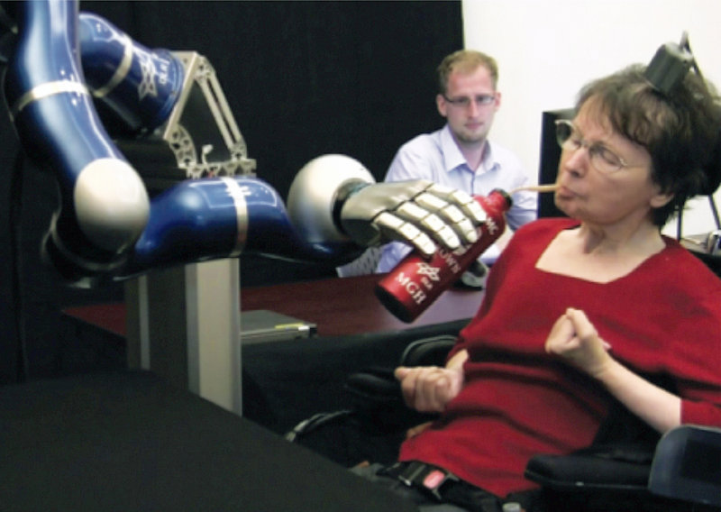 Cathy Hutchinson of East Taunton, Mass., sips a drink held by a robotic arm during a test at a long-term care residence for adults with neurological disease in Dorchester, Mass.