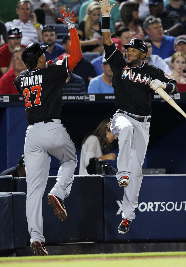 Giancarlo Stanton of the Marlins celebrates with Jose Reyes after hitting a two-run homer in the seventh Wednesday night. Miami won at Atlanta, 8-4.