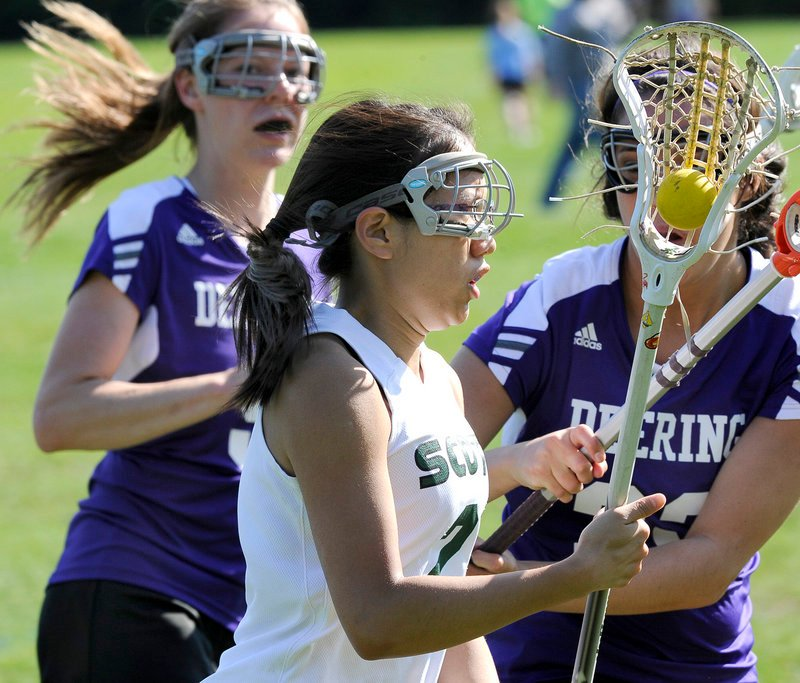 Leah Carter of Bonny Eagle advances the ball while pursued by Veronica Mitchell, left, and Casey Girsch of Deering.