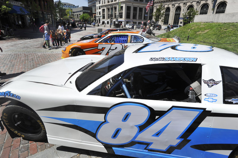 Three race cars were part of the daily rush Friday at Monument Square. Oxford Plains Speedway is opening its season with the Tour event Sunday.