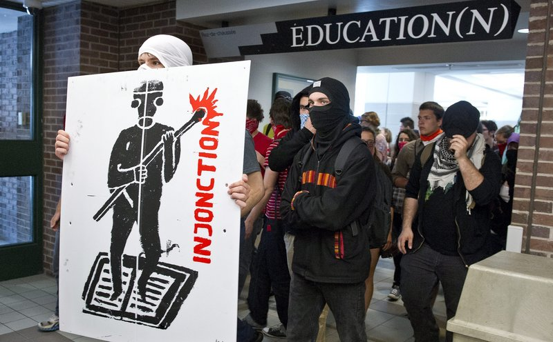 Protesters make their way through a hall at the Universite du Quebec a Montreal. Students say the new law violates their civil rights and limits their ability to oppose tuition hikes.