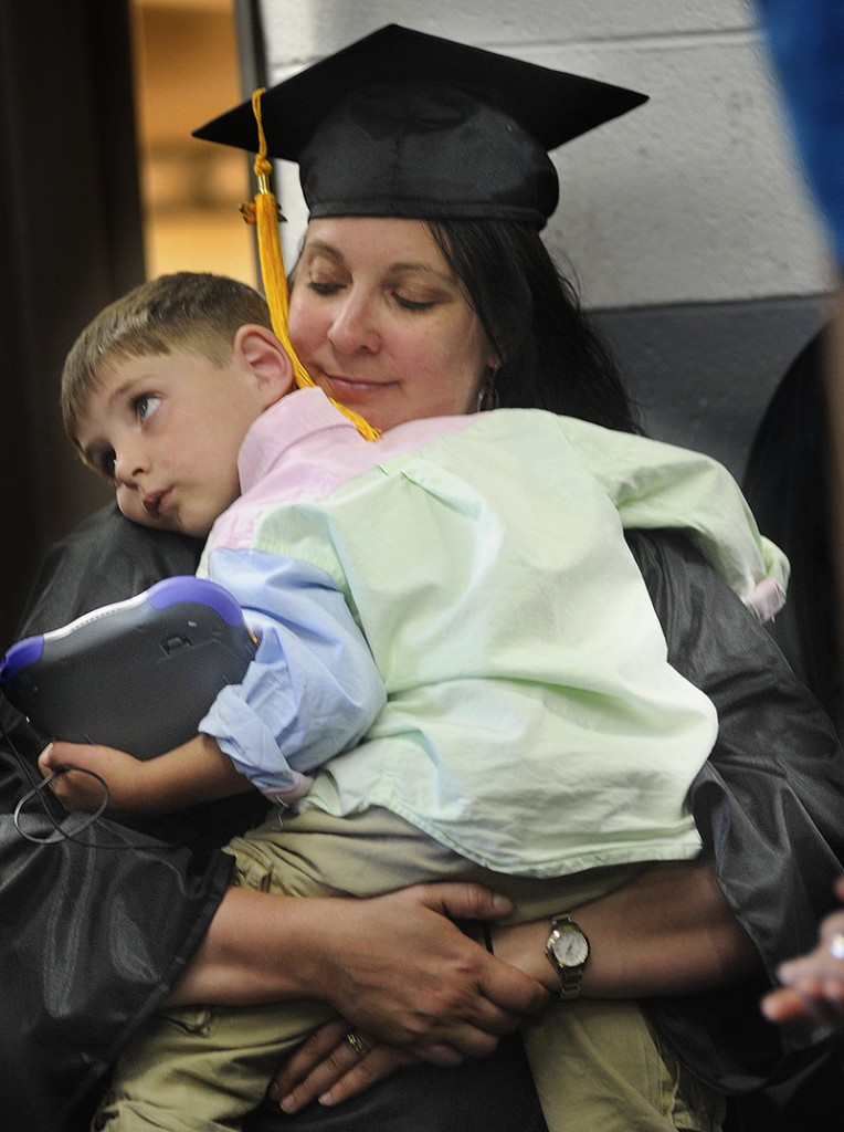 Ali Maguire of Kennebunk shares a quiet moment with her son Duncan Blanchard, 4, before marching out to receive her degree in paramedicine.