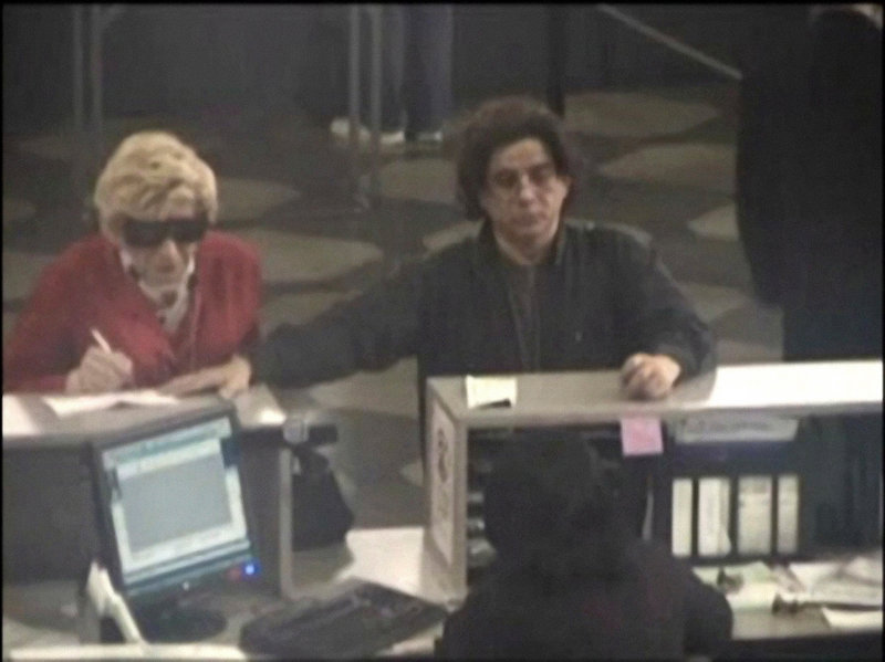 Prosecutors say this 2009 photo shows Thomas Parkin, left, on a Department of Motor Vehicles security camera, dressed as his late mother in order to collect her benefits. At right is Mhilton Rimolo, who authorities say was an accomplice.