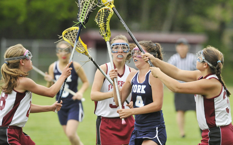 Taylor Simpson of York looks for a shot Tuesday after carrying the lacrosse ball into a crowd of Freeport defenders. Freeport tied the game late in regulation, then scored two goals in overtime and came away with a 10-9 victory.