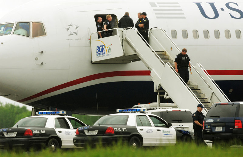 Law enforcement officials converge on a passenger jet on the tarmac at Bangor International Airport on Tuesday.