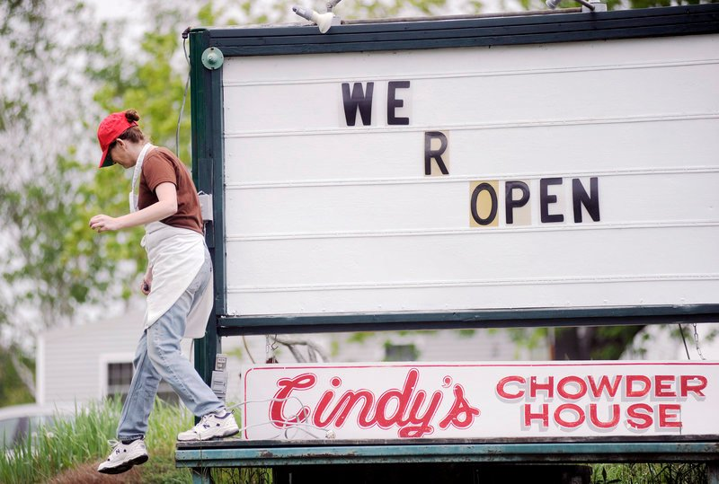 Lena Gage of Cindy's Chowder House in Freeport modifies the sign at her business on Thursday, in preparation for the tourist season that starts in earnest this holiday weekend.