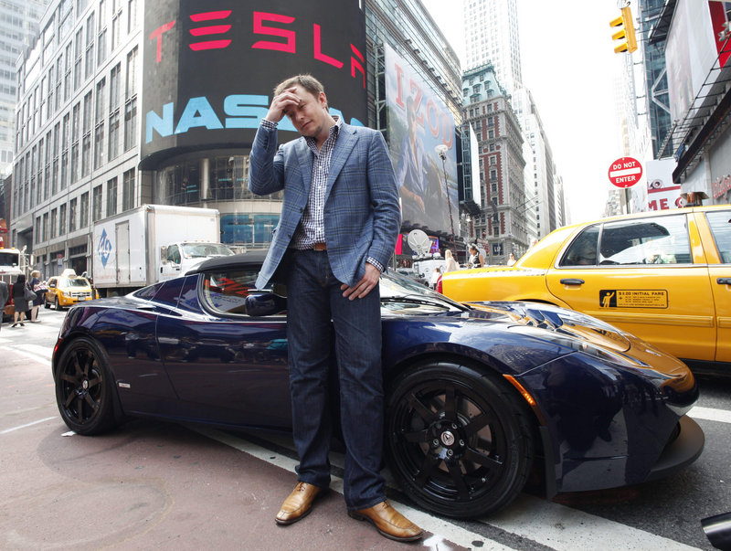 SpaceX owner and Tesla Motors CEO Elon Musk stands near a Tesla car in front of Nasdaq in June 2010. Another Tesla, the high-end, battery-powered Model S, will start being delivered to customers in late June.