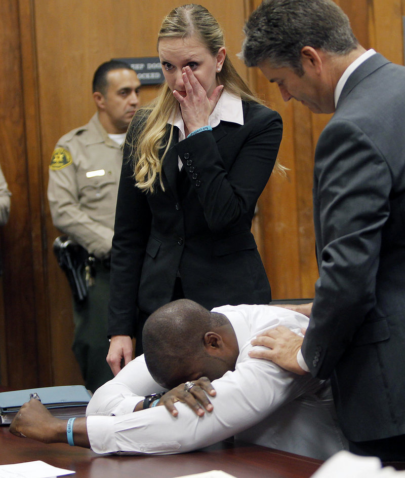 Brian Banks weeps as his attorney Justin Brooks, right, and attorney Alissa Bjerkhoel react as Banks' rape conviction is dismissed Thursday in Long Beach, Calif. A childhood friend had falsely accused him.