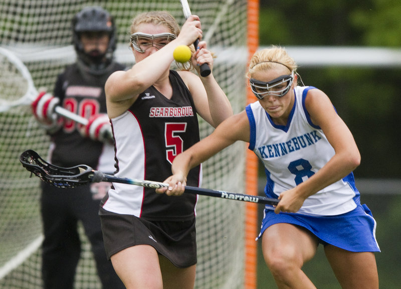 Kelsey Howard of Scarborough, left, drives the ball up the field Thursday night against Rose Bryant of Kennebunk during their schoolgirl lacrosse game. Scarborough won 9-8 and will be home throughout the Western Class A tournament.