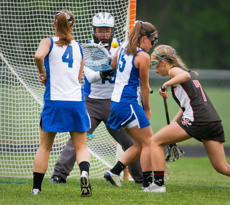 Kennebunk goalie Lizzie Stockbridge keeps her eye on the ball as teammates Sophie Auman, left, and Delaney Murphy defend against Scarborough's Kat Gadbois on Thursday. Scarborough won, 9-8.