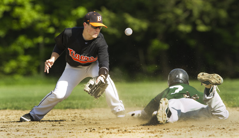 Nathan Peasley of Bonny Eagle slides safely into second for a stolen base Thursday as the throw gets past Biddeford shortstop Corey Greenleaf. Bonny Eagle scored twice in the sixth to win the Telegram League game, 3-2.