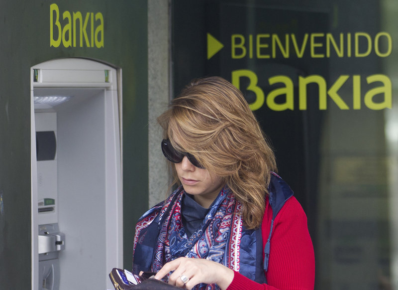 A woman uses an ATM at a branch of Bankia bank in Madrid. The bank has suffered major losses in bad loans to the real estate sector.