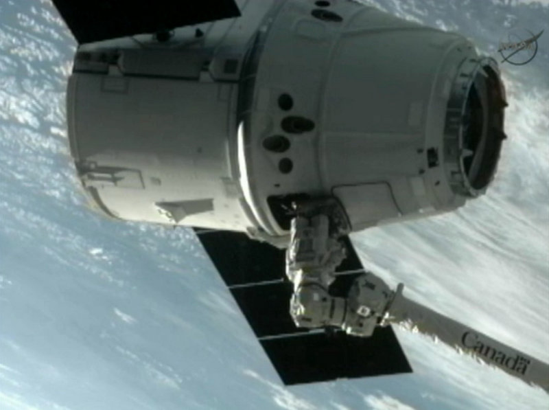 In this image provided by NASA-TV, the SpaceX Dragon commercial cargo craft is grappled by the Canadarm2 robotic arm and connected to the International Space Station on Friday.