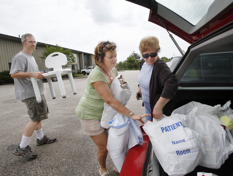Volunteer Gina Day, center, of Scarborough helps Celia McGuckian and her son Christian McGuckian of Auburn remove medical supplies from their car during a drop-off day at Partners for World Health in Scarborough.