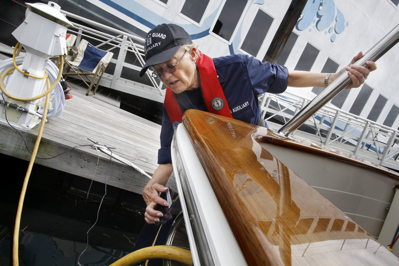 Inspector Susan Polans checks the registration numbers on a boat at DiMillo's marina in Portland on Saturday.