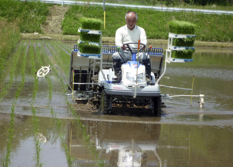 Toraaki Ogata drives a tractor to plant rice saplings in a paddy field in Fukushima, Japan, 35 miles from the Dai-ichi nuclear plant. Last year's crop sits in storage, deemed unsafe to eat.