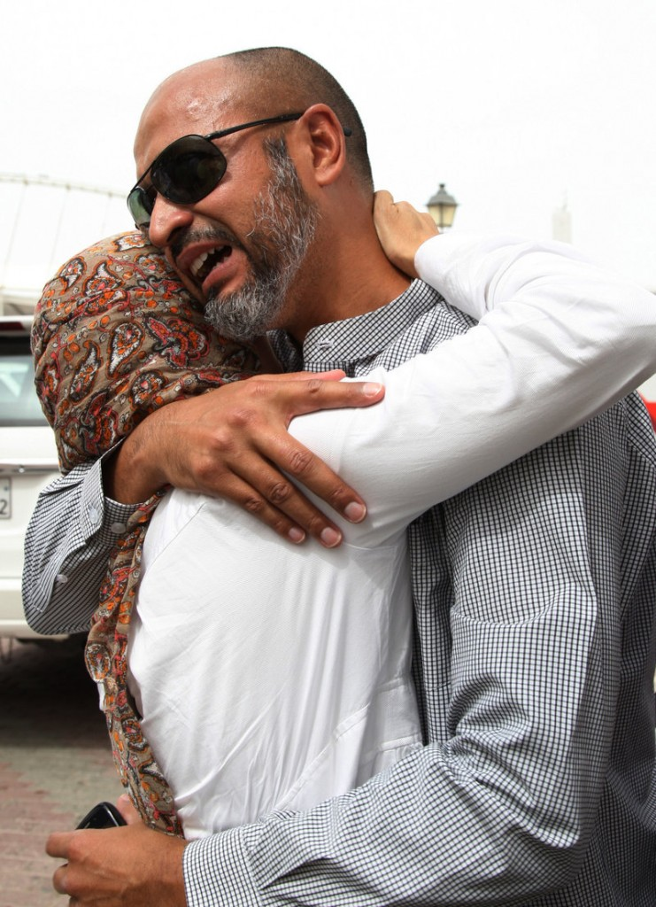 The father of a child killed in a fire at Villaggio mall in Doha, Qatar, is comforted Monday.