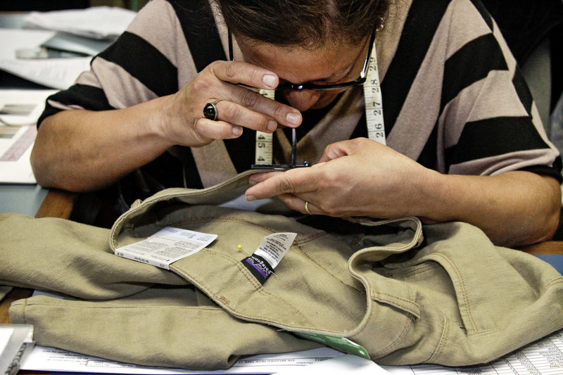 Quality-control employee Nellie Castillo counts stitches per inch on a pair of pants at Patagonia headquarters in Ventura, Calif. The company is known for well-made goods and its almost fanatical environmentalism.